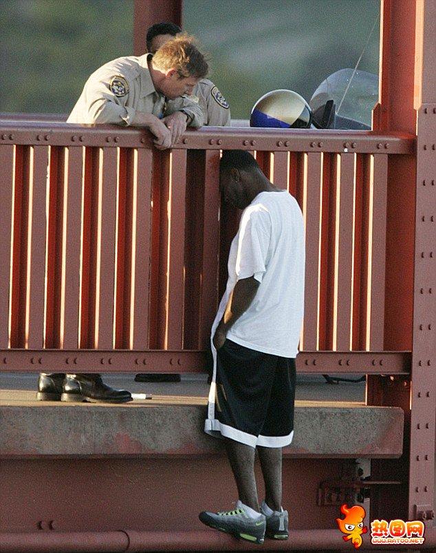 2005年,美国加州的一名高速公路巡警(左)细心地说服了右边穿白短袖的黑人男子,从而阻止了他跳桥的轻生举动。如今,这名黑人男子结了婚,而且有了两个孩子,生活得很幸福。
